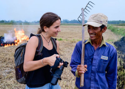 With a farmer burning rice fields
